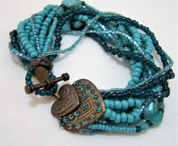 Vintage Chicos multi strand beaded bracelet 12 strands of different blue beads, aurora borealis bugle beads, turquoise glass beads, dark blue beads Decorative antiqued gold tone beaded heart toggle clasp 8 1/4 inches long Hang tag reads Chicos Better quality Chicos jewelry Very good vintage condition, shows no significant wear  International buyers welcome, overcharges are refunded Priority shipping is optional 32917  Want to see more bracelets? Click here: https://www.etsy.com...