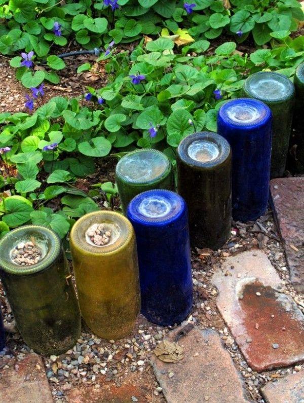 Перевернутые бутылки из-под вина - отличный способ огородить растения и украсить огород.