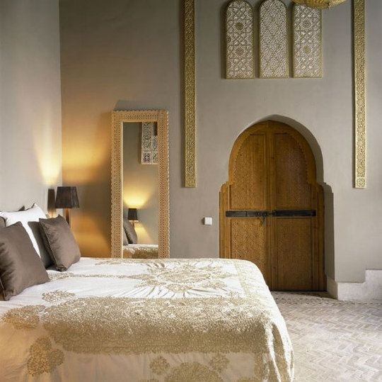 Subdued but glamorous #Moroccan bedroom with its gold embroidered bedspread and arched bedroom door. #design