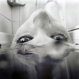 taken in the bath - waterproof camera  cool blur from the water on right hand side  great angle of the head  i like that she is looking directly at the camera   black and white makes the water really dark