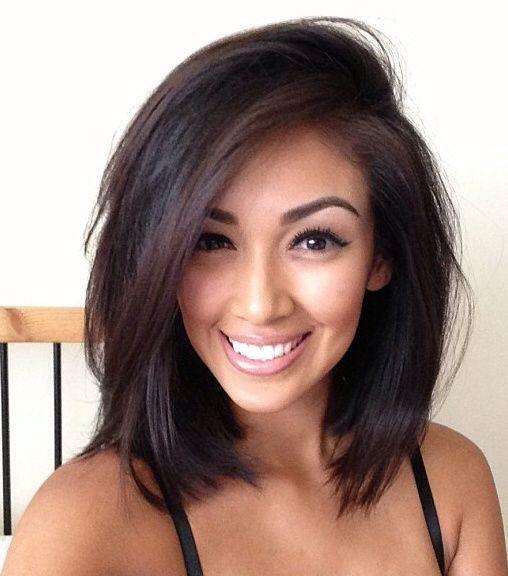 Les cheveux très foncés de cette femme ont été bien lissés et viennent joliment encadrer son visage. Le beau volume que l'on retrouve sur le dessus de la tête est une conséquence de la raie positionnée assez bas sur le côté.