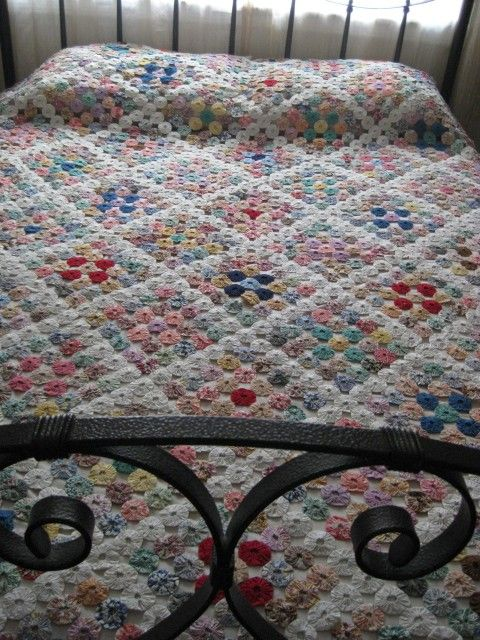 yo-yo quilt bedspread arranged in granny-squares
