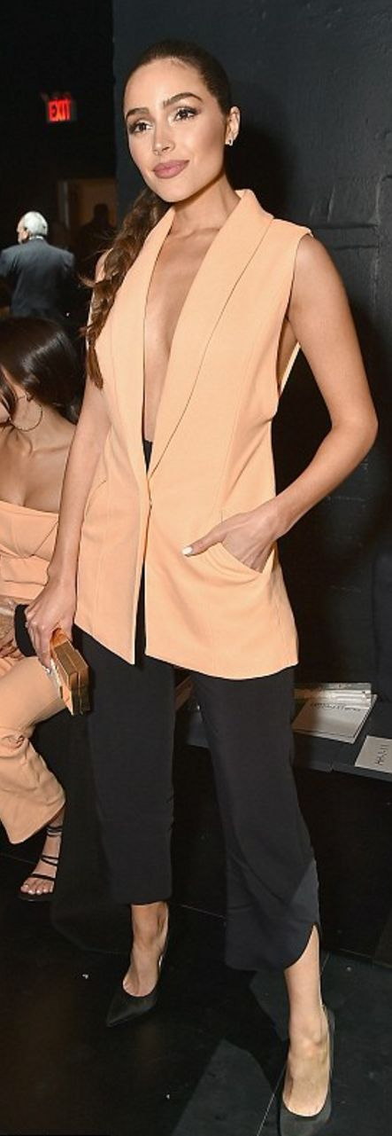 Who made Olivia Culpo's gold clutch handbag, black pants, pumps, and orange vest?