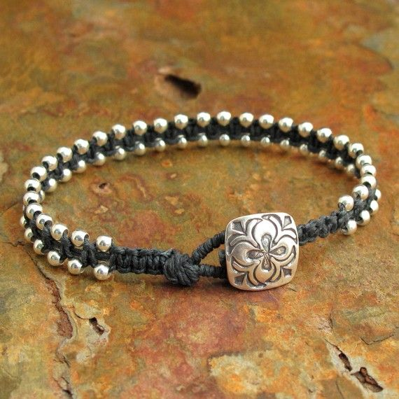 This macrame bracelet was made with charcoal gray waxed Irish linen embellished with 2 parallel rows of round sterling silver beads. Closes with a