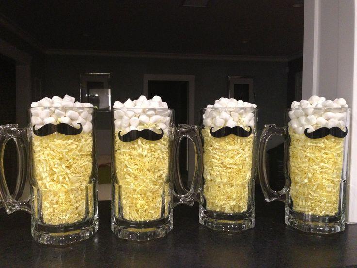 Centro de mesa con mug de cerveza decorado con bigote para el Día del Padre relleno de papel picado de color amarillo y malvaviscos. #DecoracionDiaDelPadremarshmallows.