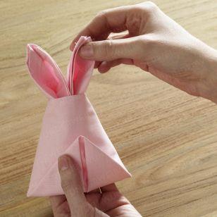 Machen Sie Ihren Ostertisch perfekt und falten Sie Stoffservietten zu einem Hasen - Mit unserer Anleitung ganz leicht.