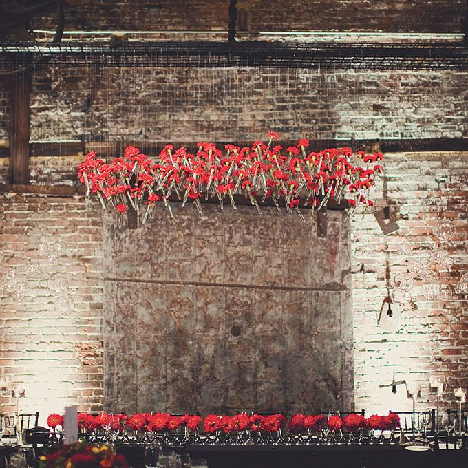 Brides.com: . Wedding centerpiece of dahlias in bud vases plus a hanging installation of red carnations in glass tubes by  Bold American Events, Atlanta Browse more red wedding centerpieces.