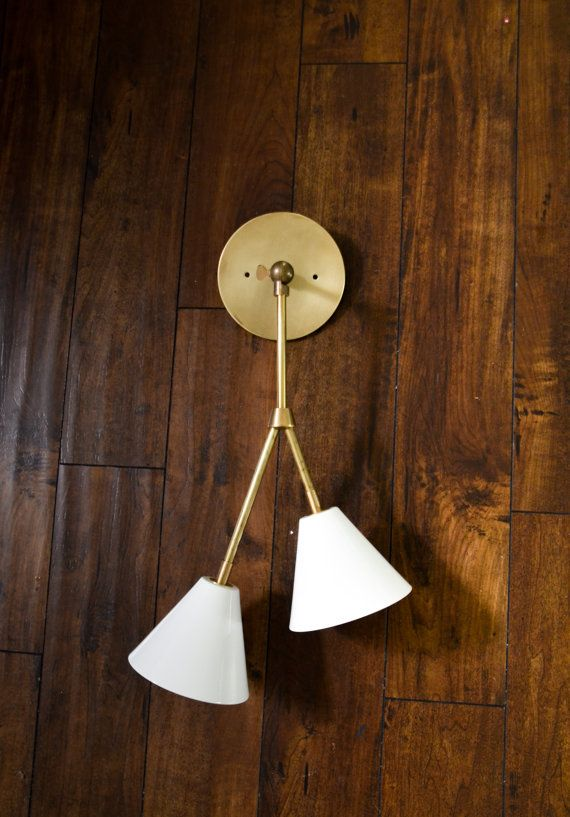 Constructed of solid unfinished brass materials, the adjustable branching double shaded tilting sconce is a fixture that can be mounted on the wall.…