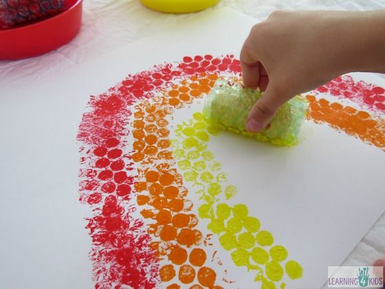 Painting a rainbow using blocks covered in bubble wrap.