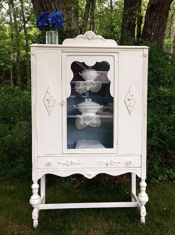 Shabby Chic Decor painted China closet! This wonderful vintage 1920s china closet is perfect for a French Cottage Home, Farmhouse Decor, Beach Cottage getaway or your Shabby Chic home! Painted the perfect shade of creamy white chalk paint, she has been lightly distressed with a topcoat of durable poly-acrylic. (washable!) We have added charming rose garland appliqués to her drawer, the top pediment and side panels. Gorgeous new crystal knobs have been added for sparkle! She has one drawer…