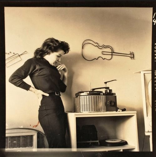 Ms. Lucky standing by a record player, from the 1950s. Credit: Bunny Yeager
