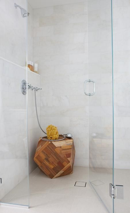 Chic walk in shower features walls clad in creamy white marble lined with a marble shelf alongside a geometric wood stool.