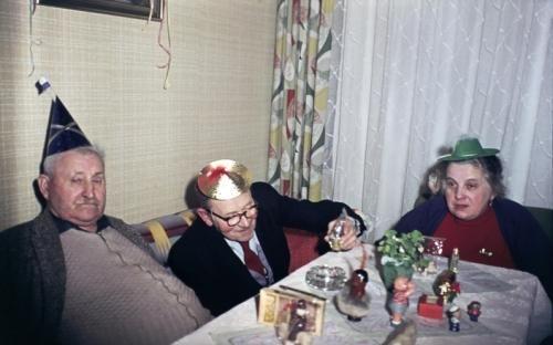 """Private Silvesterfeier: """"Bei Kaltenbachs in Spandau. Vater Kaltenbach, Papa und Mama, mit Hütchen"""", schreibt der Fotograf zu diesem Bild vom Jahreswechsel 1960/1961. Es sollte für lange Zeit das letzte Silvester sein, das er im Westen der Stadt verbringt. Signatur im Bundesarchiv: N 1648 Bild-KD04276"""