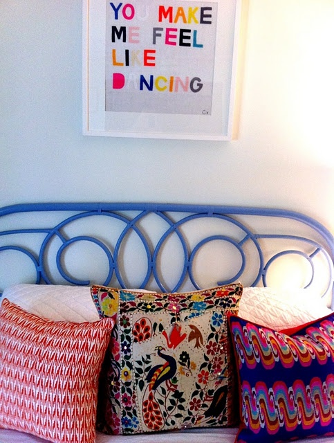 Pretty deep blue metal headboard with nicely patterned pillows