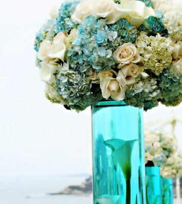 Light aqua or Tiffany blue centerpiece with blue and white hydrangeas and white roses and a teal glass vase with a calla lily inside, very nice, very pretty