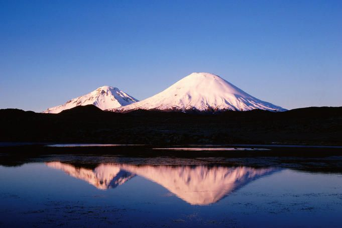 Parinacota and Pomerape volcanoes at sunset, with reflection in high-altitude lake, Norte Grande region. Chile
