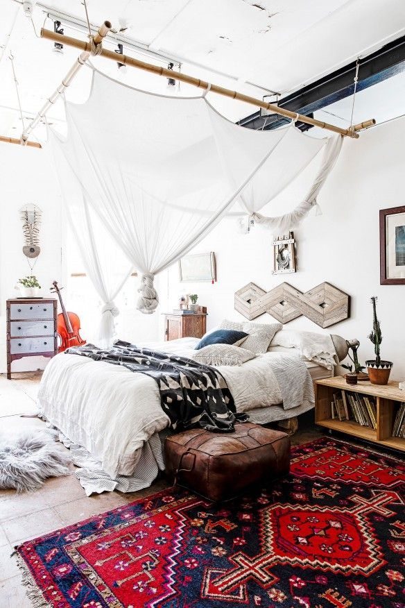 A bold, bright rug mixed with a creative but subtle canopy make this bedroom's decor quite unique.