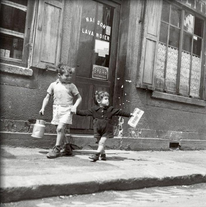 On allait chez le crémier, le pot à lait en aluminium à la main, acheter le lait au litre.    / By Robert Doisneau, Rue Marcellin Berthelot, Choisy-Le-Roi, c.1945.