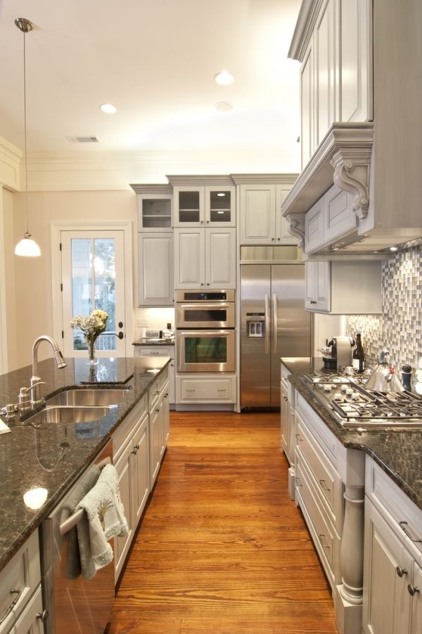 I love the tile on the wall and how the cabinets have furniture details. Love the grey color scheme.