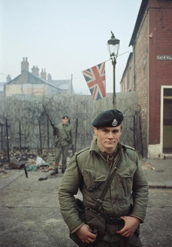 2nd Lieutenant Robin Martin (foreground) with Rifleman O'Reilly of 1st Royal Green Jackets, man a street barricade in Belfast during the Battalion's first tour of duty in Northern Ireland. The tour lasted from 20 August - 18 December 1969. Note the Union Jack flag flying from a lamp-post.