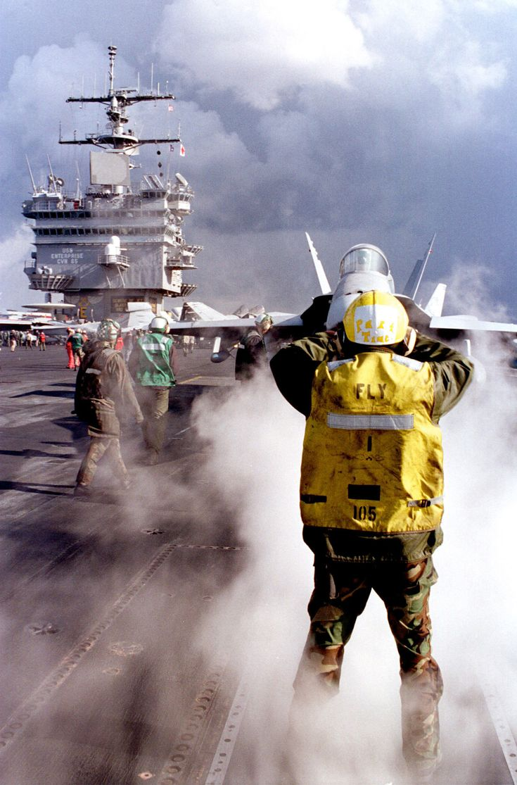 An F/A- 18 Hornet is directed by a yellow shirt to the forward port catapult on the flight deck of the of USS Enterprise (CVN 65) as the ship conducts flight operations in the Mediterranean Sea on Feb. 11 1999. [1500  2274]