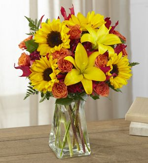 The FTD® Harvest Heartstrings™ Bouquet brings sunlit autumn beauty straight to their door. Unforgettable mini sunflowers catch the eye at every turn surrounded by yellow Asiatic lilies, red dianthus, orange spray roses and lush greens to create a stunning fresh flower arrangement.