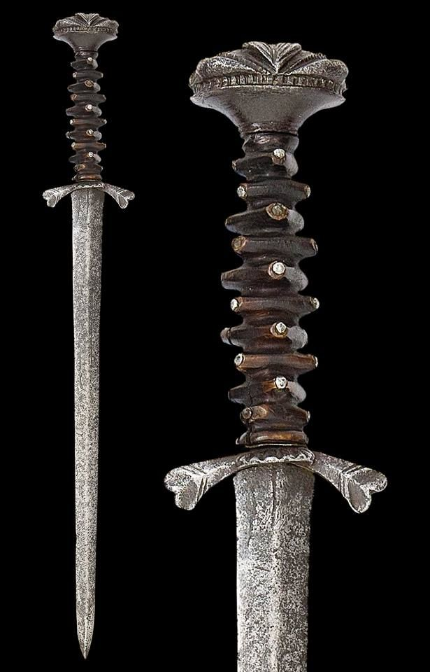 Description: Rare Landsknecht Dagger, With tapering double-edged blade of flattened diamond section, iron hilt comprising short down-curved quillons with heart-shaped tips within incised lines and small shell-guard on one side, cushion-shaped pommel cut with fan-shaped flutes and ovals on each side, and one-piece dark horn grip of compressed triangular cushions heightened at each corner with an iron pin, a shim of brass at the base, Origin, German, Date: First Half of the 16th century