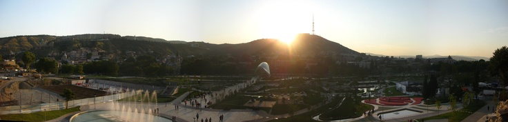 Millennium Park at sunset in Tbilisi, Georgia. The Bridge of Peace is visible just under the sun.