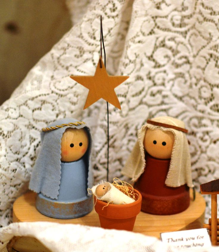 Anyone can make these. Small terracotta pots painted with wooden balls and your choice of fabric. For the baby Jesus use a small clothes pin.