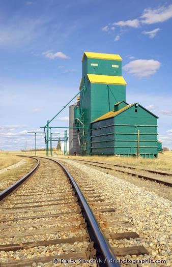 A green grain elevator towers over railroad tracks and the grassy prairies in Southern Alberta.