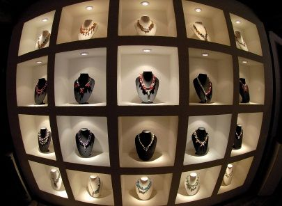 Jewelry lighting wall showcase with puck lights which call attention to individual pieces by putting a spotlight on individual pieces and creating a silhouette.