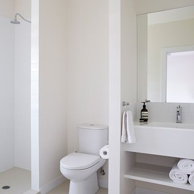I like the use of dividing walls in this all white bathroom.