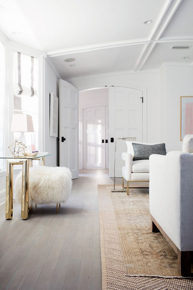 Glam, minimalist living space with layered area rugs, architectural details on the ceiling, a white armchair, and a lamb stool
