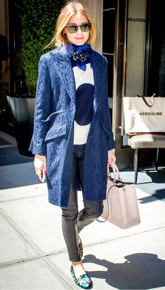 Olivia Palermo dresses up a graphic sweater and leather leggings with a blue coat and scarf tied around her neck