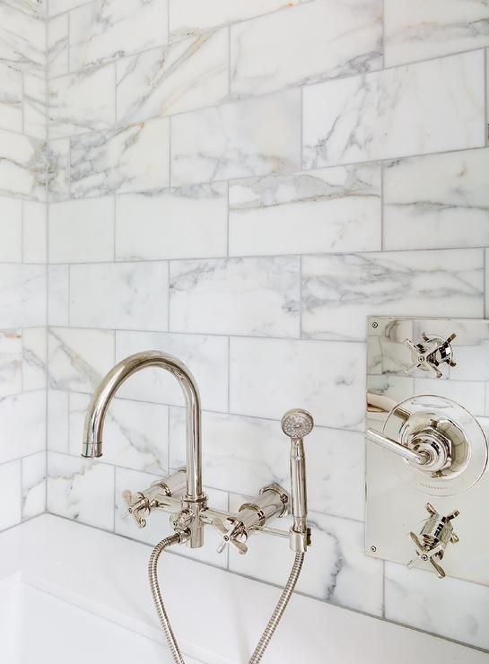 Absolutely gorgeous bathroom boasts a gooseneck tub filler by Waterworks mounted on a marble tiled wall placed over a sleek bathtub.