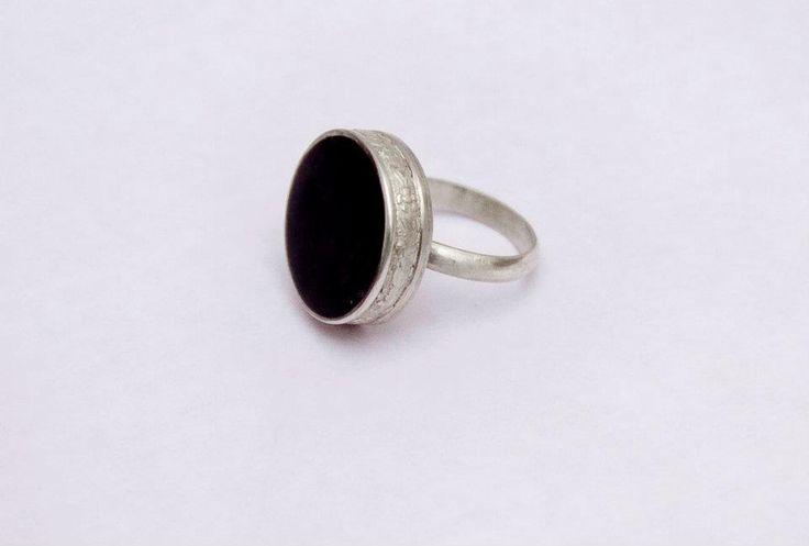 Este anillo está confeccionado en plata 925 con una delicada guarda de flores como detalles. El círculo tiene un reconstituido de ébano.Se realiza a pedido.