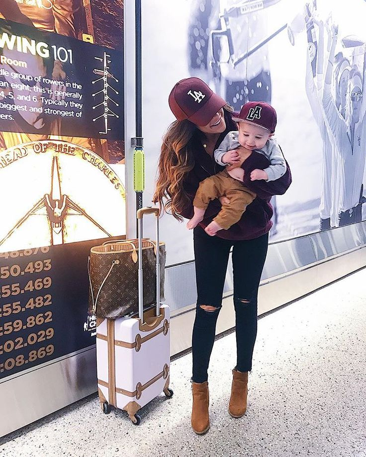 Wine colored pullover | Black Ripped Denim | Booties | Cap | cute airport travel outfits | Travel Outfit | Airport outfit | baby and mommy casual airport travel outfits. Emily Gemma, The Sweetest Thing Blog #thesweetestthing #emilyanngemma. Emily Gemma.