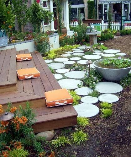 Concrete circle stepping stones and large concrete planter with low plants…