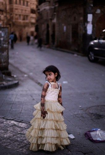 delucazade:    A Yemeni girl wearing a new dress as she stands in an alley of the old city, on the first day of the Muslim holiday of Eid al-Adha, or Feast of the Sacrifice, in Sanaa, Yemen.  Muhammed Muheisen/AP