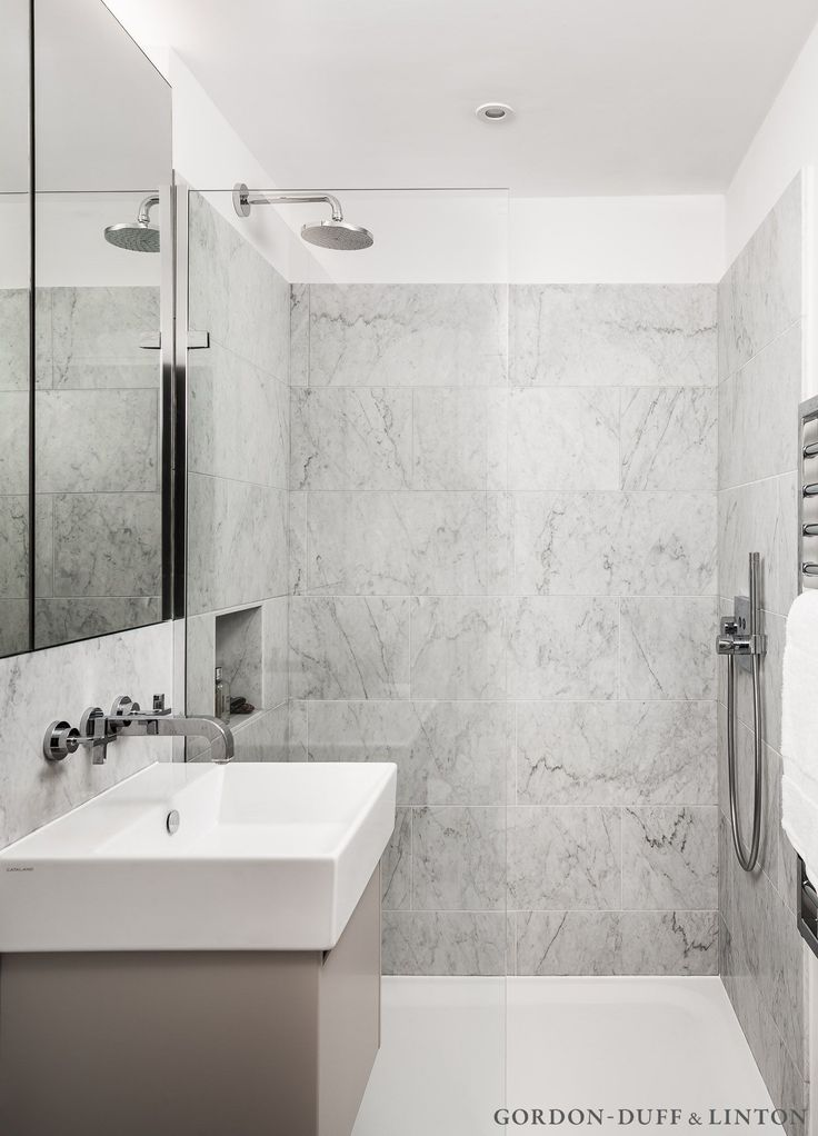 Carrara marble tiles and Hansgrohe wall mounted taps in shower room.