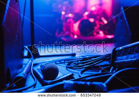 Microphone and cable lying on the stage before the show in blue light
