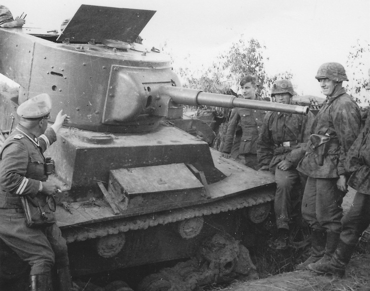 "Grenadiers of the Waffen SS Division ""Totenkopf"" examine a Soviet T-26 tank knocked out in battle. Note the NCO on the left pointing to details of the hull."