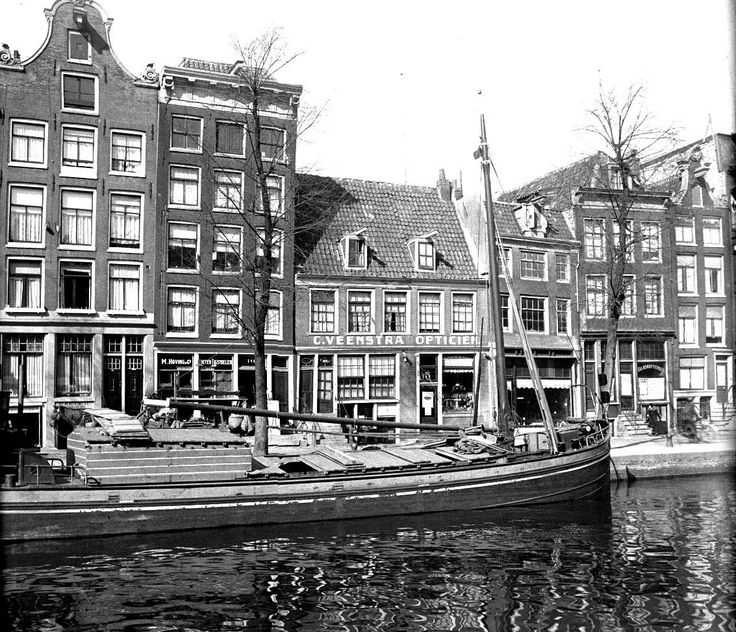 1931. A view of the Prinsengracht between the Bloemgracht and Nieuwe Leliestraat in the Jordaan neighborhood of Amsterdam. From left to right the basket weaving business of M. Hoving and the optician store of C. Veenstra. The Prinsengracht is one of the four main canals of Amsterdam. The construction was started in 1612 at the initiative of Mayor French Hendricksz and was part of the third expansion of the city. Photo Stadsarchief Amsterdam. #amsterdam #1931 #Prinsengracht #Jordaan