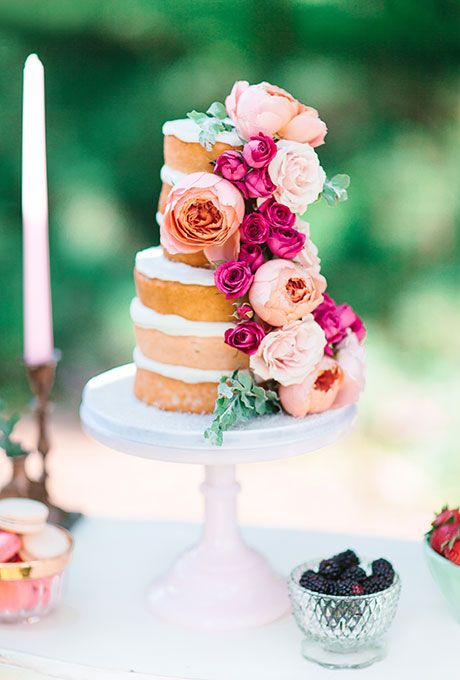 A two-tiered naked wedding cake decorated with pink peonies and roses created by @DreamSliceCakes | Brides.com: