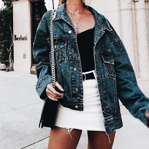 Oversized denim jacket over black top and white denim mini skirt.