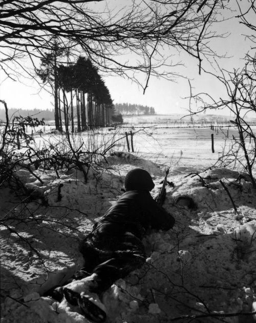 An Army GI sits patiently in the snow during the Bulge. Note the snow on his shoes....