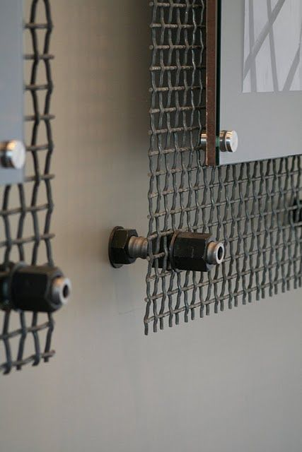 lobby photos hung by metal grids that the construction company uses to separate rocks in their rock pit.