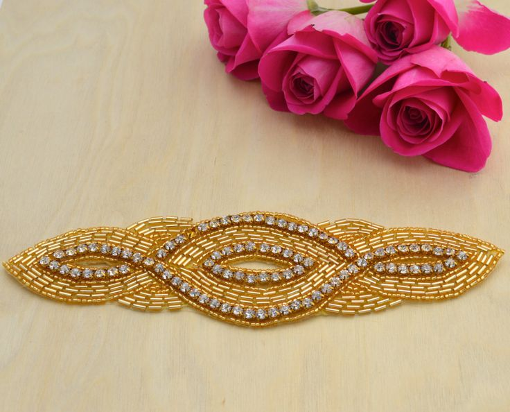 Beads and rhinestones are intertwined to create a memorable and elegant appliqué that can be added to any garment or head piece.  Also Available in Silver https://www.etsy.com/listing/195681220/long-and-elegant-applique-with-beautiful?ref=related-0  The beads and rhinestones are intricately placed on a iron-on material for easy and convenient application.   Easily and conveniently make your own head piece by attaching/gluing the appliqué onto a comb or a hea...