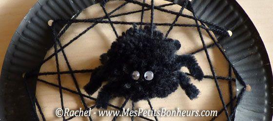 Bricolage enfants - araignée pompon sur sa toile en laine. Assiette ou dessus de boîte à chaussures
