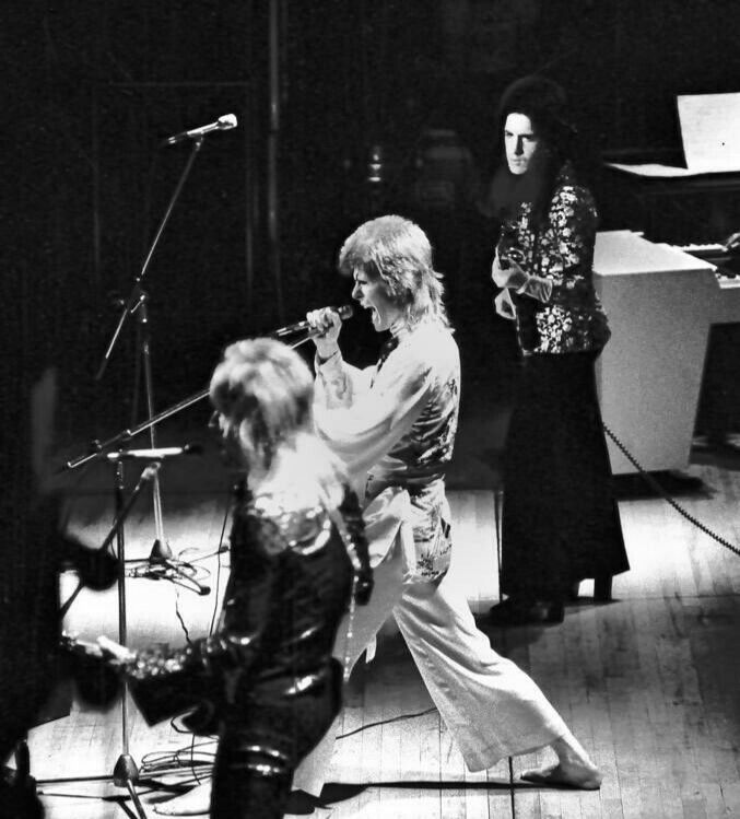David Bowie performing on stage with Trevor Bolder and Mick Ronson